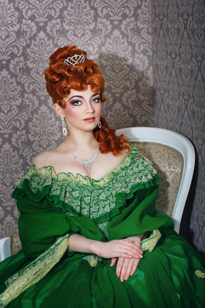Attractive young girl in green gown and red wig photo
