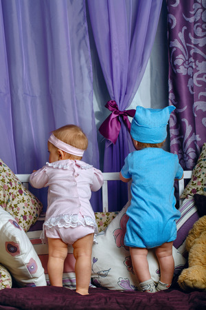 Brother and sister in the nursery are on the cradle turned to the window waiting for the arrival of parents photo