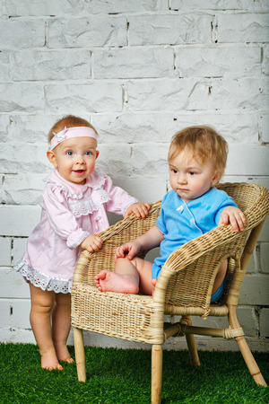 Brother and sister playing in the backyard next to the wicker chair photo