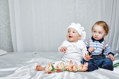Cute brother and sister playing on a bed with silk sheets in the nursery