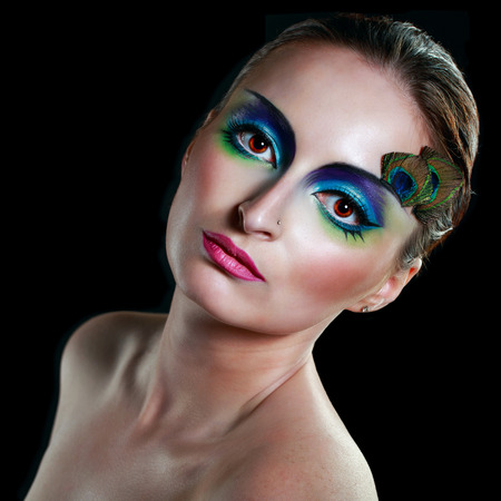 Attractive young girl with makeup peacock bird closeup portrait photo