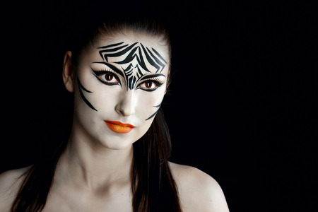 Attractive young girl with make-up of wild zebra close-up portrait