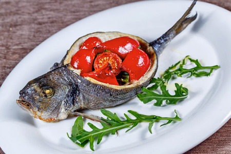 Appetizing fried fish dorado with vegetables closeup shot photo