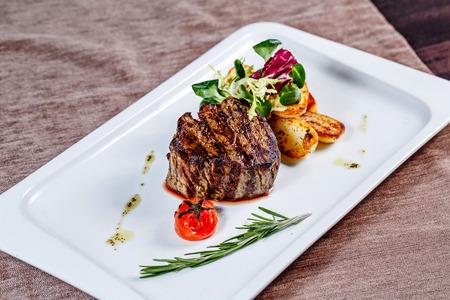 Steak with garnish in a restaurant on a white plate closeup shot