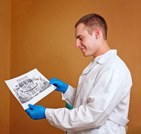 Young specialist dentist in your workplace holding orthopantomogram patsienta photo