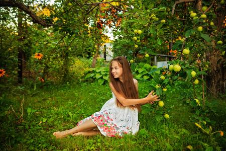 Cute teen girl walks barefoot in the garden near the apple tree photo