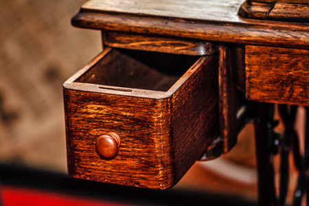 Retractable drawer is pulled out. Vintage oak table closeup shot photo