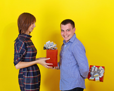 Young cheerful couple gives each other gifts for the holiday photo