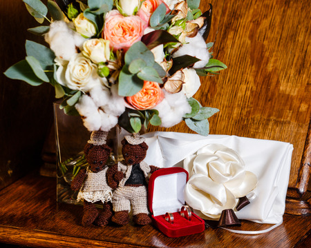 Wedding rings in a red box next to the flowers closeup shot photo