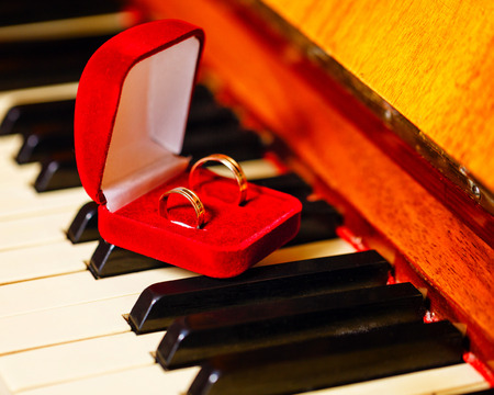 Wedding rings in a red box standing on the piano keys closeup shot photo