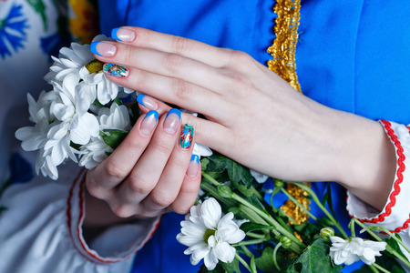 Beautiful female hands with manicure holding flowers close-up shot