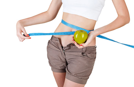 Young slim girl measures the waist after exercising isolated on white background photo