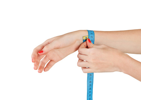 Young slim woman measures the wrist after sports isolated on white background