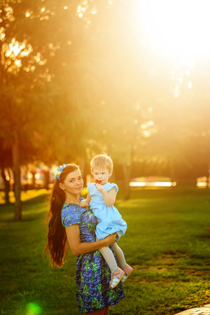 Young mother holding daughter in her arms a city park photo