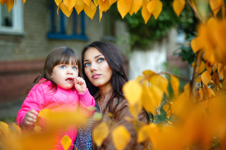 Young mother holding daughter in his arms in a city park in autumn photo