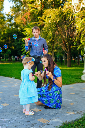 outsiders: Happy family of mother, father and daughter walk in autumn park and blow bubbles