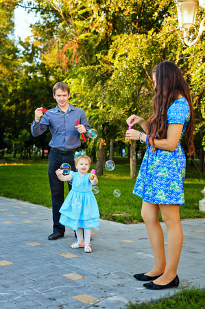 outsiders: Happy family mother, father and daughter walk in autumn park and blow bubbles