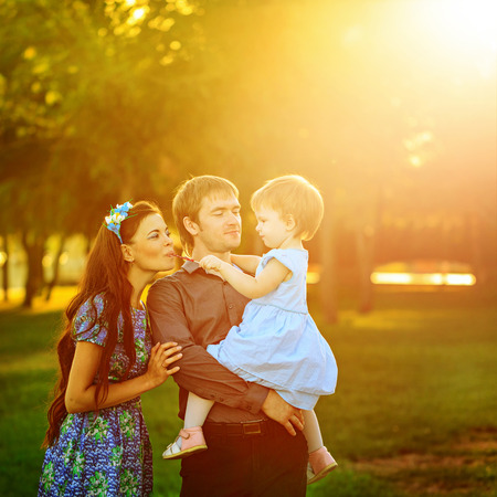 outsiders: Happy family of mother, father and daughter walk in autumn park Stock Photo