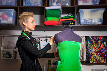 Fashion designer working with dummy and cloth photo