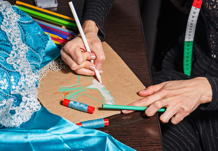 Fashion designer draws a sketch of the future dress on paper, beside lie thread and lace