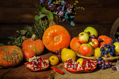 Still life harvest festival of fresh and ripe fruits and vegetables: pumpkin, apples, pears, grapes and pomegranates Stock Photo