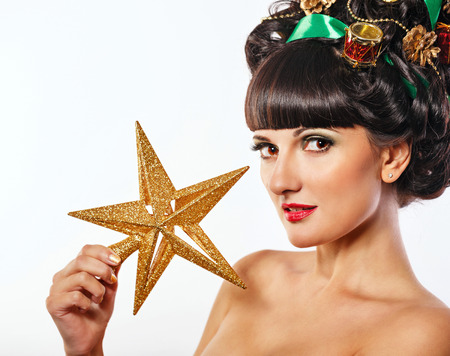 upsweep: Young attractive girl with creative hairdo holding decorations for Christmas trees Stock Photo
