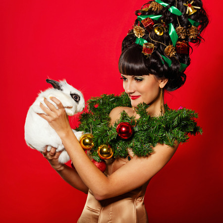 upsweep: Young attractive girl with creative hairdo hairstyle Christmas holding a rabbit