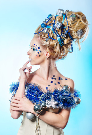 upsweep: Young attractive blonde girl with creative hairdo christmas close-up portrait