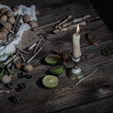 charms: Still life of ingredients for making potions witch. Nuts, sticks, scrolls, thread, runes, charms, pumpkin, lime, lemon, pine cones and other ingredients lie on a wooden table.