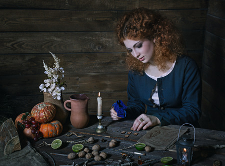 The red-haired witch preparing a potion from a variety of ingredients, spread on a wooden table. Picture toned.
