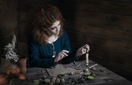 shemale: The red-haired witch preparing a potion from a variety of ingredients, spread on a wooden table. Picture toned.