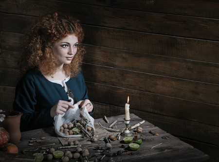 exorcist: The red-haired witch preparing a potion from a variety of ingredients, spread on a wooden table. Picture toned.