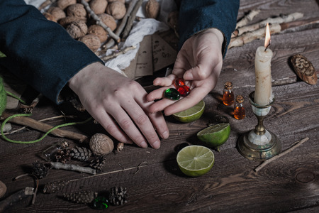 bewitchment: Hands Witch, close-up, cooking potion from a variety of ingredients, spread on a wooden table. Stock Photo