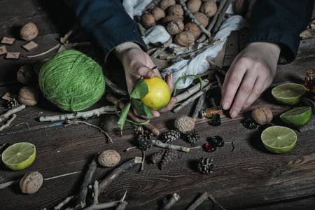 Hands Witch, close-up, cooking potion from a variety of ingredients, spread on a wooden table. Stock Photo