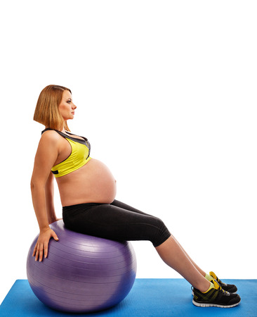 Beautiful pregnant woman doing exercises with fitball on white background photo