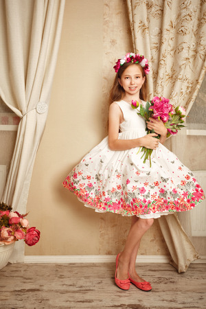 Little cute girl with doll appearance dressed in a beautiful dress. Stock Photo