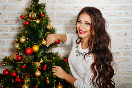 Photo of a beautiful girl with long hair decorated Christmas tree photo
