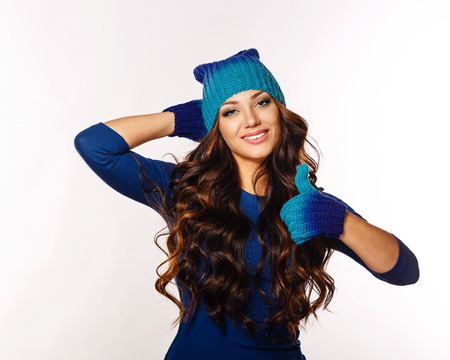 Photo of a beautiful girl with long hair and knitted things, showing thumbs up photo