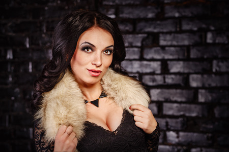 Portrait of beautiful brunette woman in black dress and furs.  photo