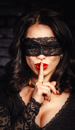 Mysterious girl in a mask put her index finger to her lips silent. photo