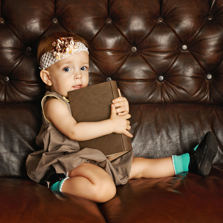 Little cute girl with big book sitting on a leather couch photo