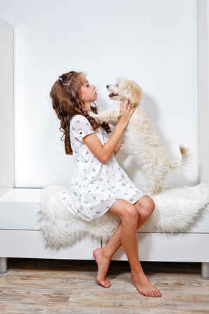Little cute girl and dog in home interior photo