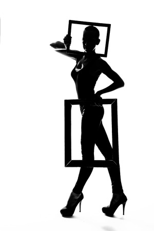 playful behaviour: Silhouette fashion slim girl dancing in high heels with frame