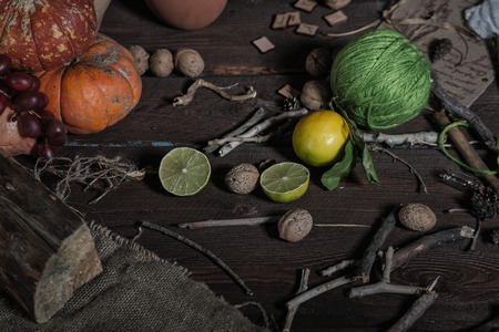 Still life of ingredients for making potions witch. Nuts, sticks, scrolls, thread, runes, charms, pumpkin, lime, lemon, pine cones and other ingredients lie on a wooden table. photo