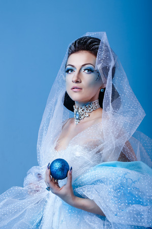 Attractive young girl with a theatrical makeup on the face in the image fabulous snow queen photo
