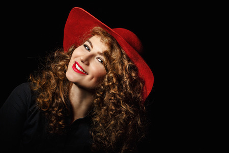 elegancy: Portrait of a beautiful woman with long curly hair in a red hat