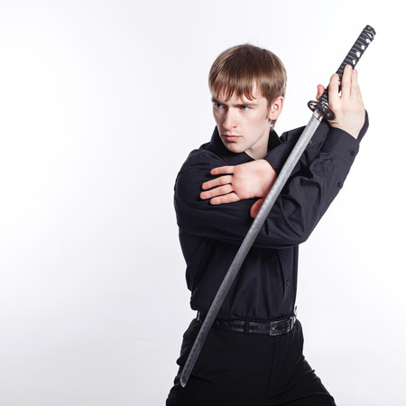 Man in shirt and trousers holding a katana. The concept of modern aggressive businessman photo