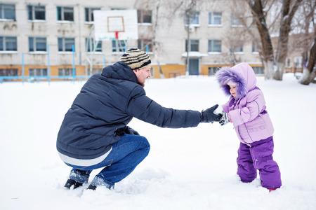 snowballs: Giovane padre e figlia scolpiscono palle di neve nel parco d'inverno in una giornata di sole. Archivio Fotografico