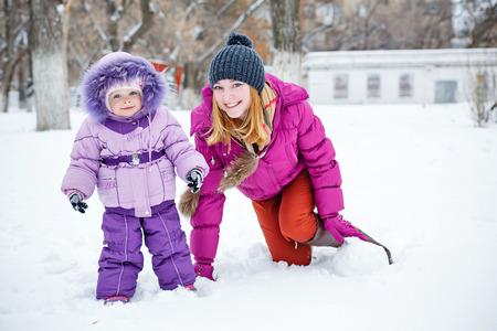 Young mother and daughter laughing for a walk in winter park photo