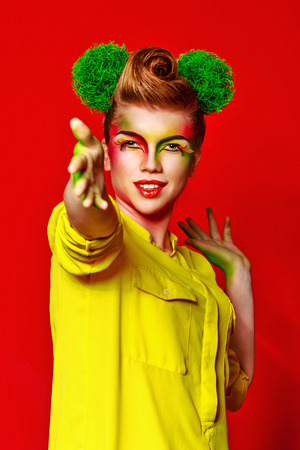 merrymaking: Cheerful girl with make-up broccoli demonstrates positive emotions. Concept of healthy food and organic products. Stock Photo